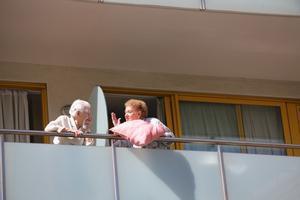 Dos ancianas charlan en el balcón de una residencia.