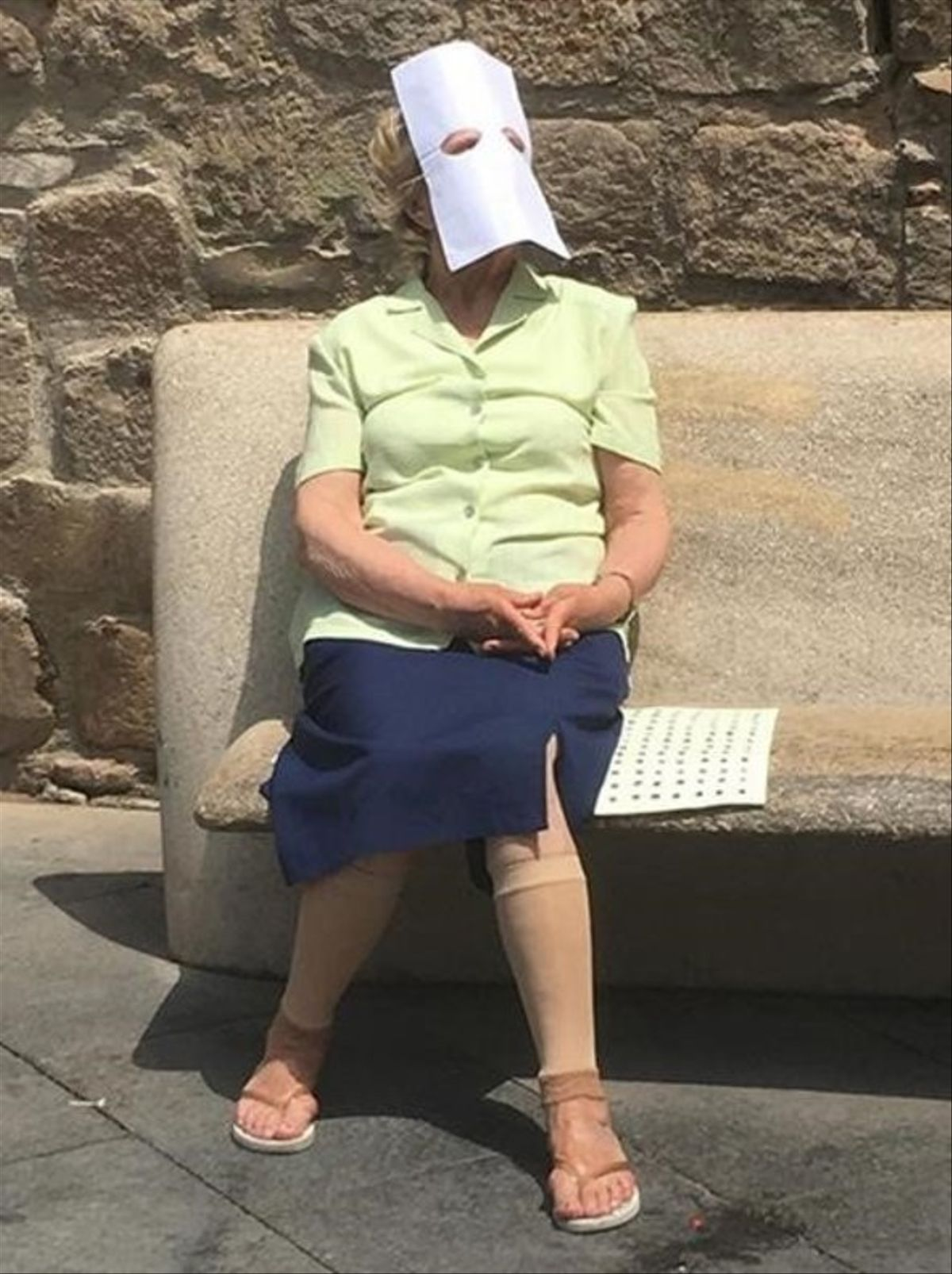 Una mujer enmascarada toma el sol en la plaza del Macba. Viernes 13 en versión Din A-4.