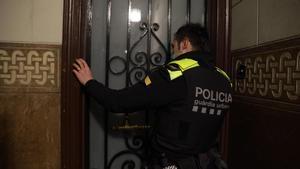 Un agente de la Guardia Urbana llama a un domicilio tras recibir el aviso de un vecino, en Barcelona.