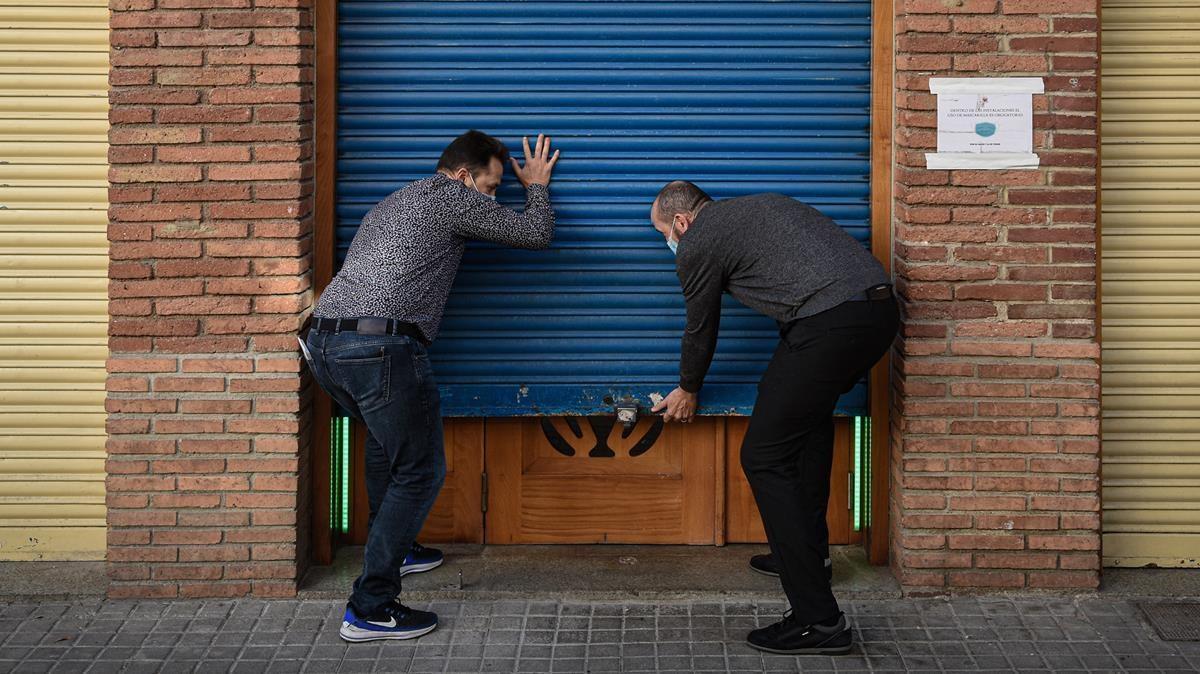 Barcelona 22 11 2020 Barcelona   Preparatius apertura bars terasses etc    angel y javi  hijos de Silvestre  propietario del renombrado restaurante Salamanca  abren la persiana de su local  AUTOR  Manu Mitru