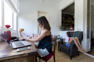 Una mujer teletrabaja en casa.