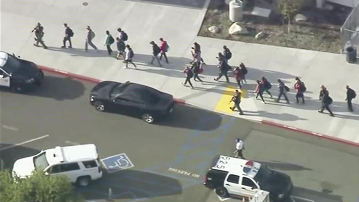 Varios agentes evacuan a los estudiantes del instituto de Los Ángeles.
