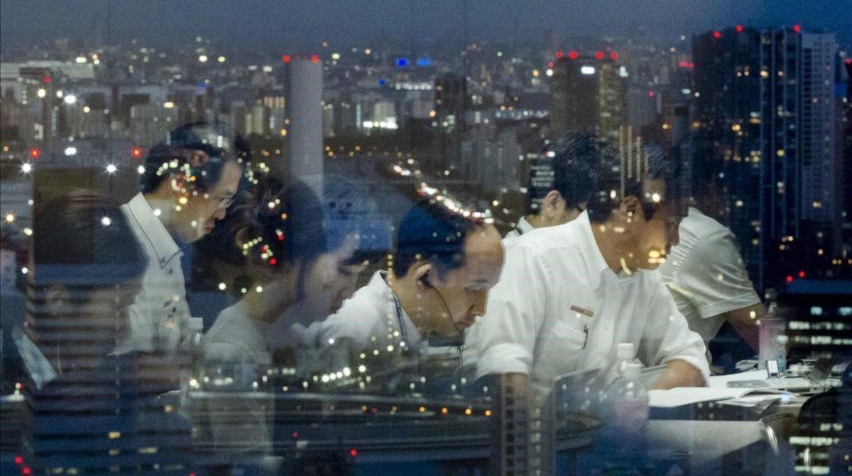 Empleados japoneses trabajando a altas horas de la noche en una empresa tecnológica con sede en Tokio.