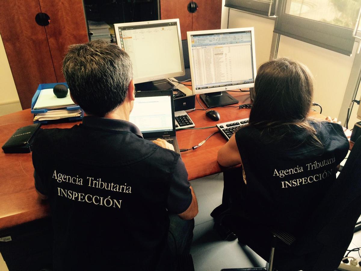 Dos inspectores de la Agencia Tributaria, analizando datos en sus ordenadores.