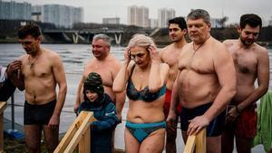 Un grupo de ortodoxos rusos se disponen a sumergirse en el agua en Moscú, en la celebración de un rito