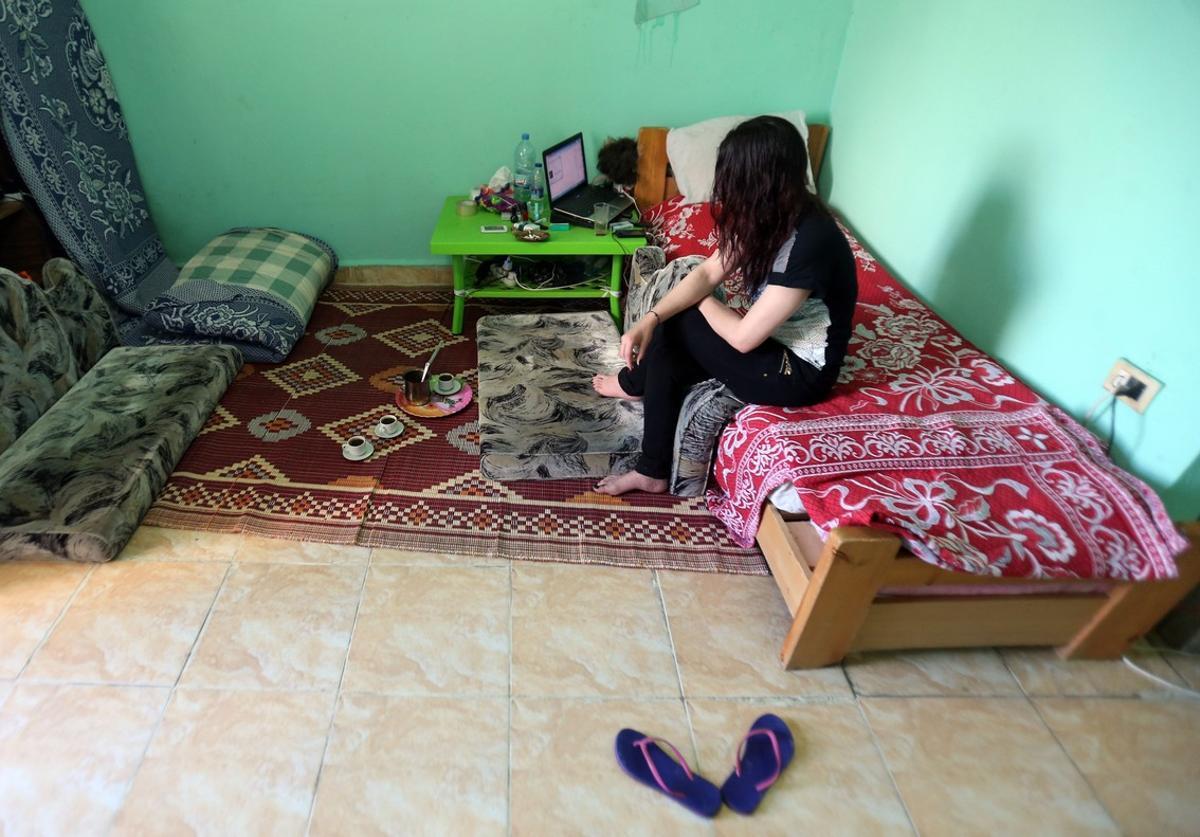 Una víctima siria de la red de prostitución libanesa, sentada en la cama de una habitación, en su actual refugio tras escapar del burdel.