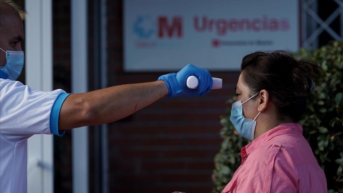 Un sanitario tomando la temperatura antes de hacer la prueba PCR, en San Sebastián de los Reyes
