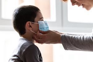 Una madre coloca a su hijo una mascarilla un día después de que el presidente del Gobierno, Pedro Sánchez, haya confirmado en una rueda de prensa que los niños podrán salir a la calle con condiciones a partir del 27 de abril, en Vitoria/Euskadi (España) a 19 de abril de 2020.