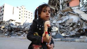 Una niña frente a unas casas destruidas tras un ataque aéreo israelí, en Gaza.