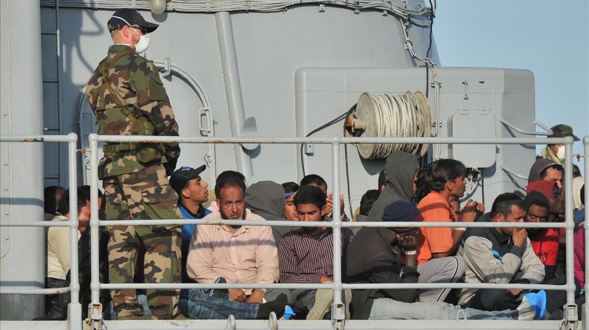 Inmigrantes rescatados porun barco militar francés en el puerto deCrotone, en el sur de Italia.