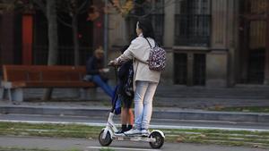 Una mujer lleva a un menor en un patinete eléctrico, a mediados de noviembre, en Barcelona.