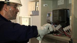 Un técnico instala unos contadores de la electricidad.