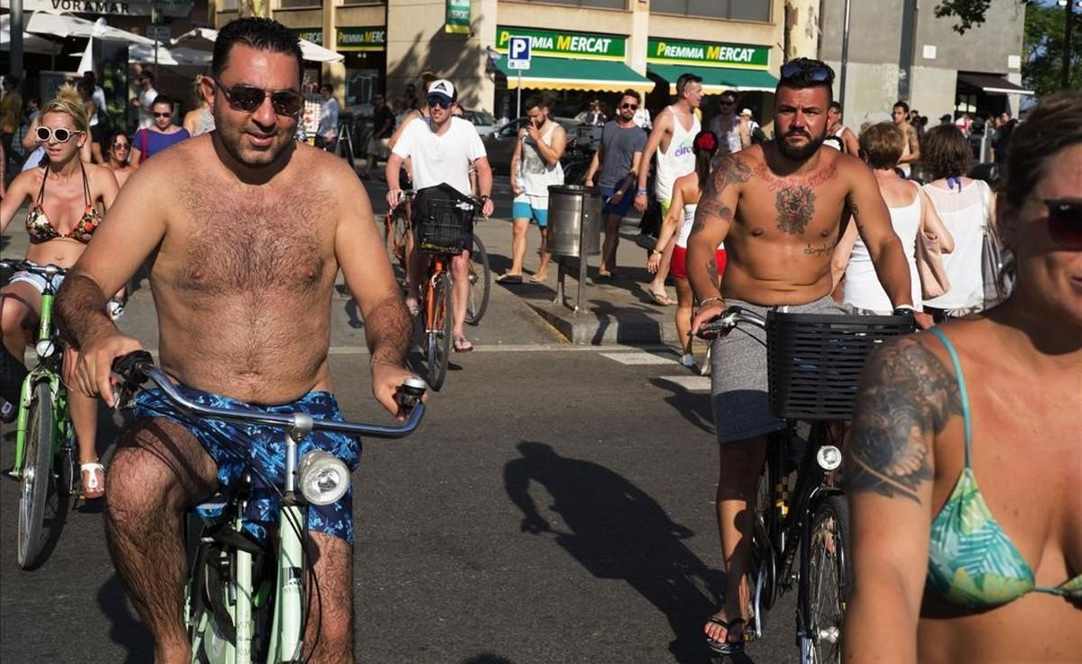 Un grupo de turistas pedaleandoen bañador por la ciudad.