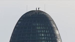 Dos personas se encaraman a la torre Agbar y se hacen un selfie