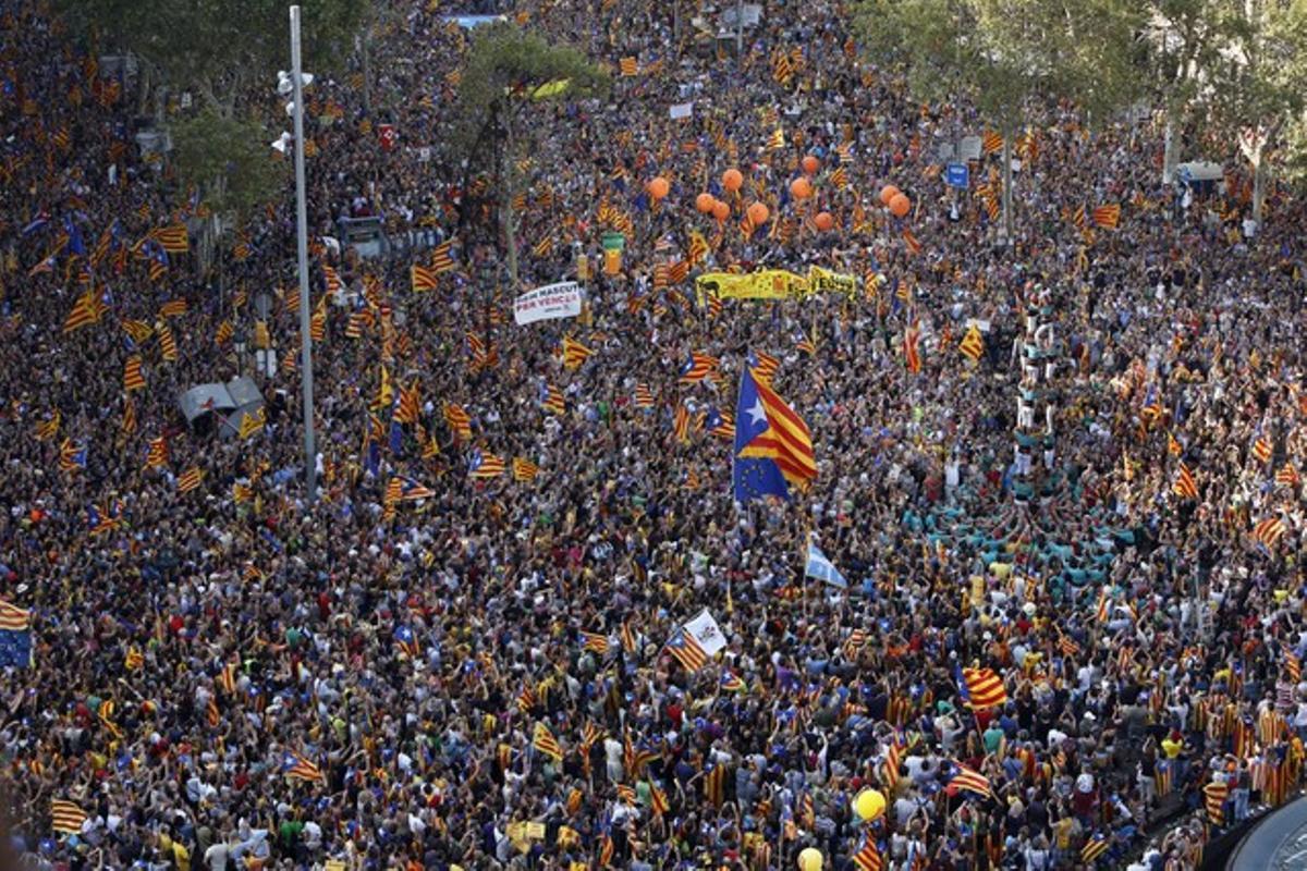 Mentre esperen que comencila manifestació, centenars de milers de persones observen una torre de castellers al passeig de Gràcia amb Gran Via.