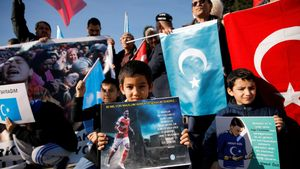 Ethnic Uighur boys hold placards with the images of English soccer club Arsenal's midfielder Mesut Ozil during a protest against China in Istanbul, Turkey December 14, 2019. The placard reads: Thank you, Mesut Ozil, on behalf of 35 million oppressed.  REUTERS/Kemal Aslan NO RESALES. NO ARCHIVES