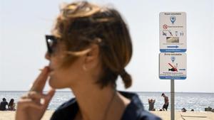 Una joven da una calada antes de entrar a la zona delimitada libre de humos en la playa de Masnou.