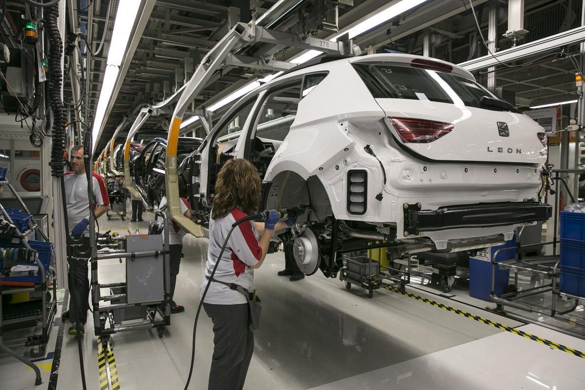 Unos operarios trabajan en la cadena de montaje de la planta de Seat, en Martorell.