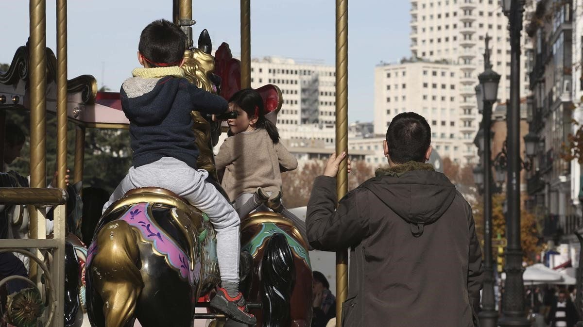 Unos niños montan en un tiovivo en presencia de adultos, en Madrid.