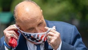 (FILES) In this file photo taken on July 01  2020 Rudy Giuliani  attorney for US President Donald Trump  puts on a mask after speaking at the White House in Washington  DC  - Donald Trump on December 6  2020 tweeted that his personal lawyer Rudy Giuliani  who has led the president s effort to undo his election loss  tested positive for Covid-19  (Photo by JIM WATSON   AFP)