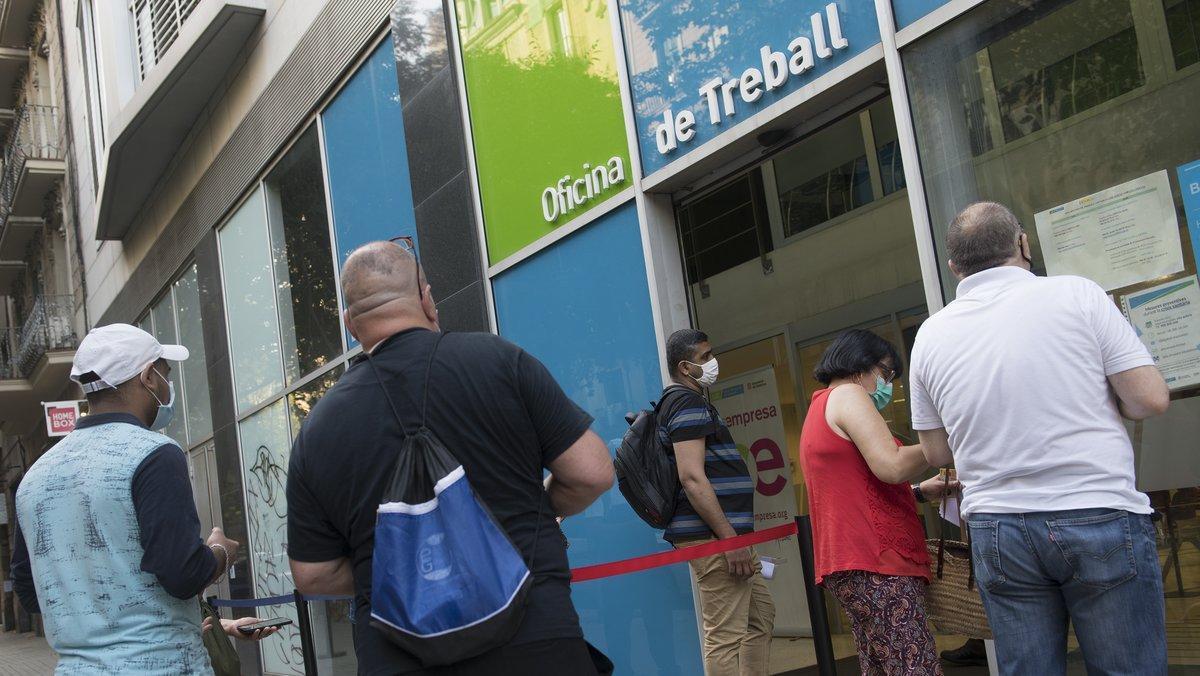 Personas en paro hacen cola frente a una oficina del SEPE en Barcelona para ser atendidos.