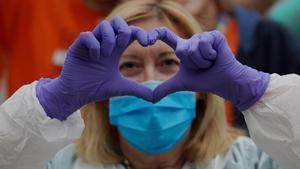 Una enfermera del hospital Gregorio Marañón, de Madrid, hace el signo del corazón con sus manos para agradecer los aplausos a los sanitarios.