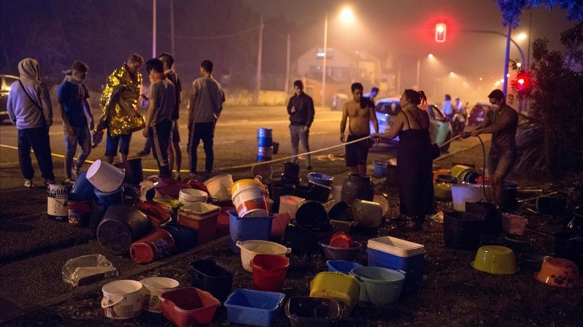 Ciudadanos de Vigo sofocan con cubos de agua un fuego en la ciudad.