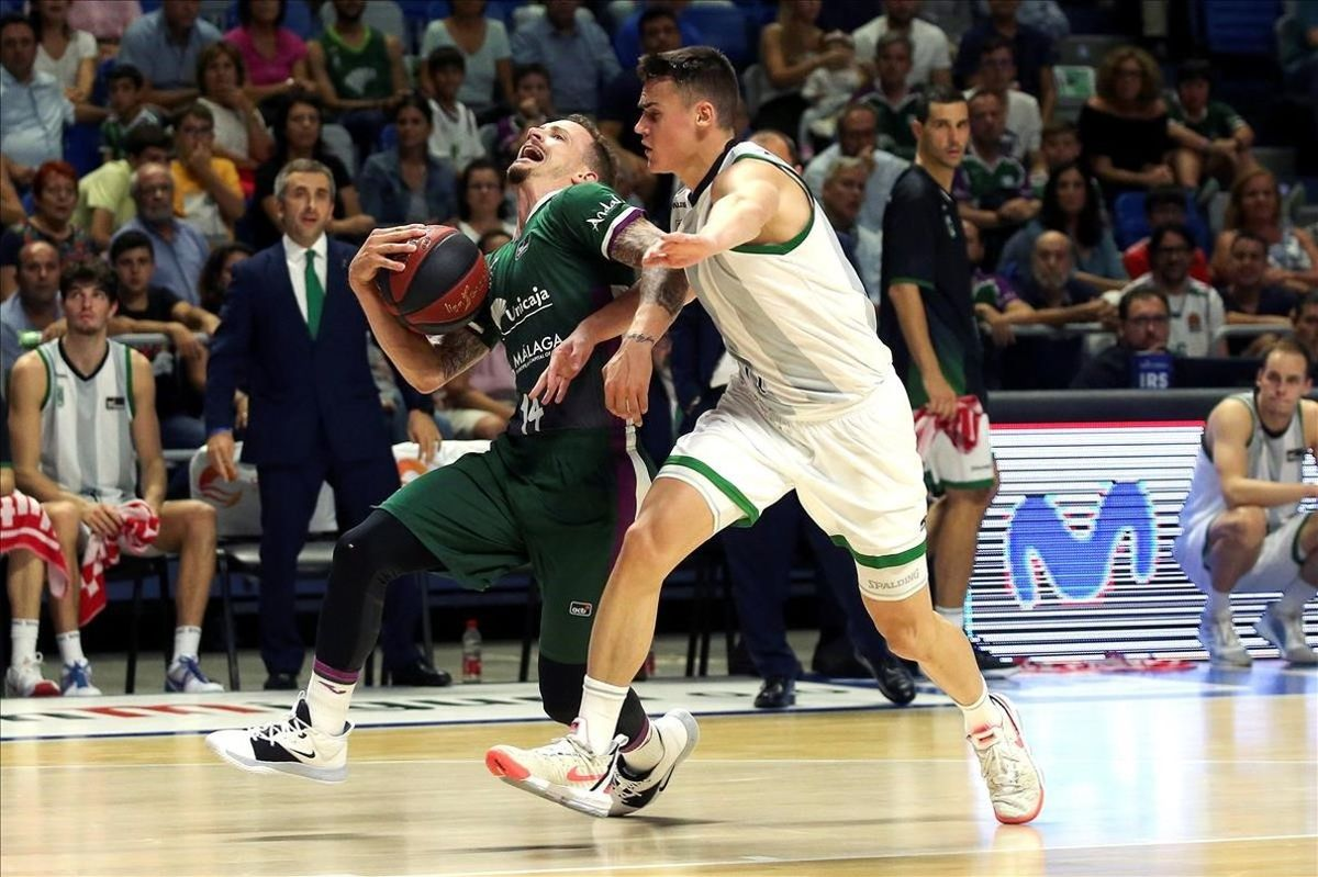 El base del Unicaja, Adams, pugna con el de la Penya, Dimitrijevic, por el control de un balón