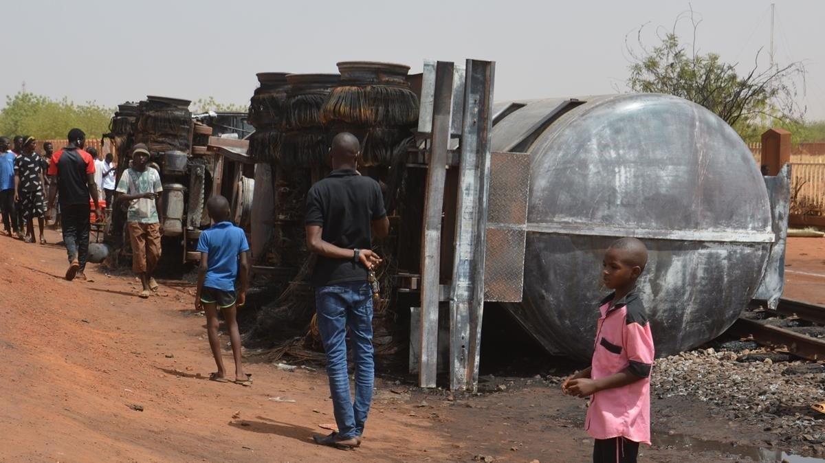 Un grupo de personas junto al tanque de combustible que estalló y mató a al menos 58 vecinos cerca del aeropuerto de Niamey.