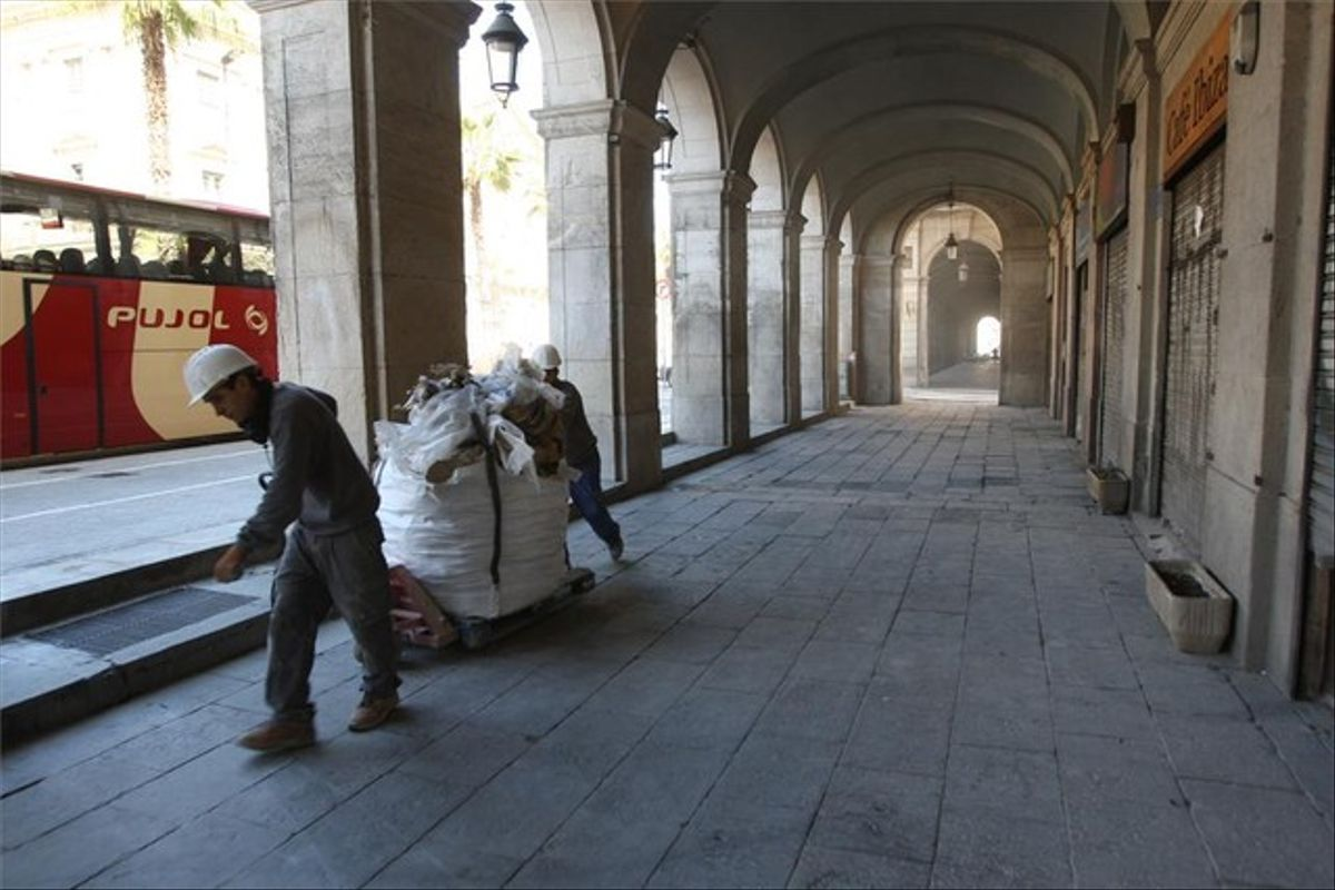 Dos obreros retiran una bolsa llena de escombros de una de las fincas en rehabilitación del entorno de los porches de Xifré.
