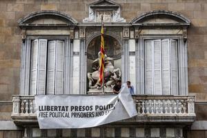 Dos trabajadores de la Generalitat retiran la pancarta.