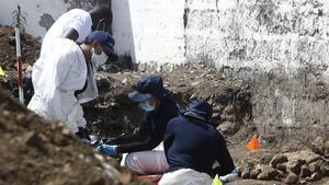 Expertos forenses de la JEP llevan a cabo labores de exhumación en el cementerio de Dabeiba, en el noroccidente de Colombia, en una fosa común donde fueron hallados restos de víctimas de los 'falsos positivos'.