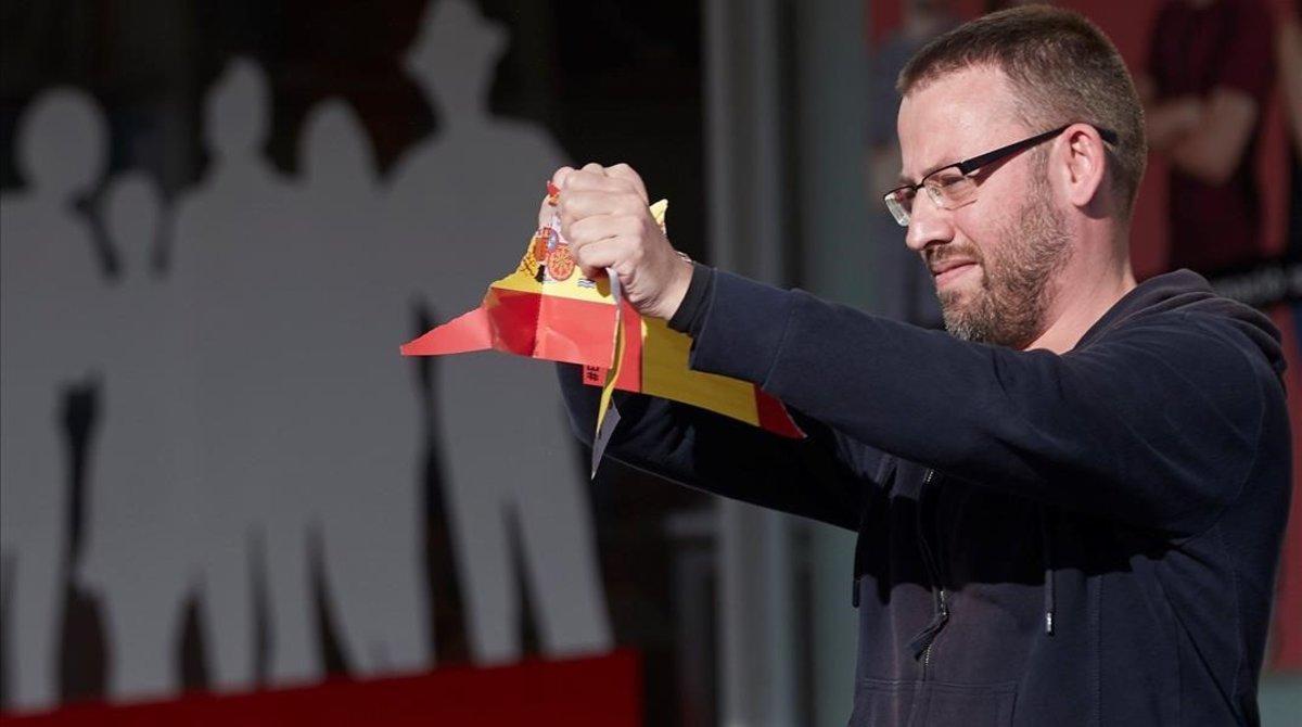 El diputado de la Cup Vidal Aragones rompe una bandera en la UAB durante un actoantifacista en la universidad.
