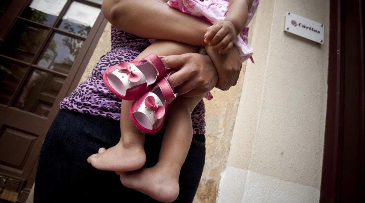 Una madre, junto a su hija, en el centro maternoinfantil de Cáritas en Badalona.