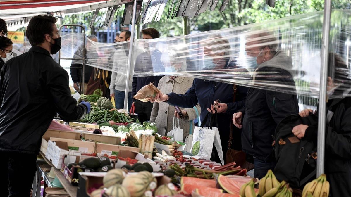 Un vendedor de frutas y verduras atiende a los clientes detrás de una protección de plástico en el mercado Place des Fetes en París.