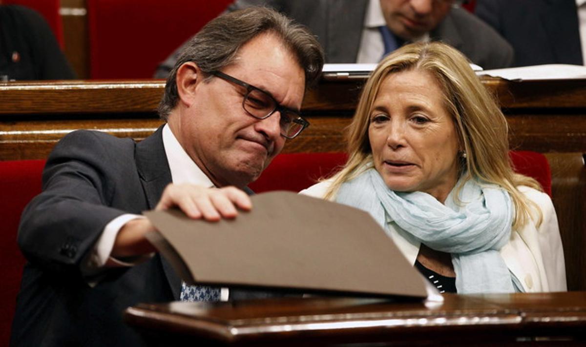 Artur Mas mira bajo una carpeta en el Parlament, junto a la vicepresidenta Joana Ortega.