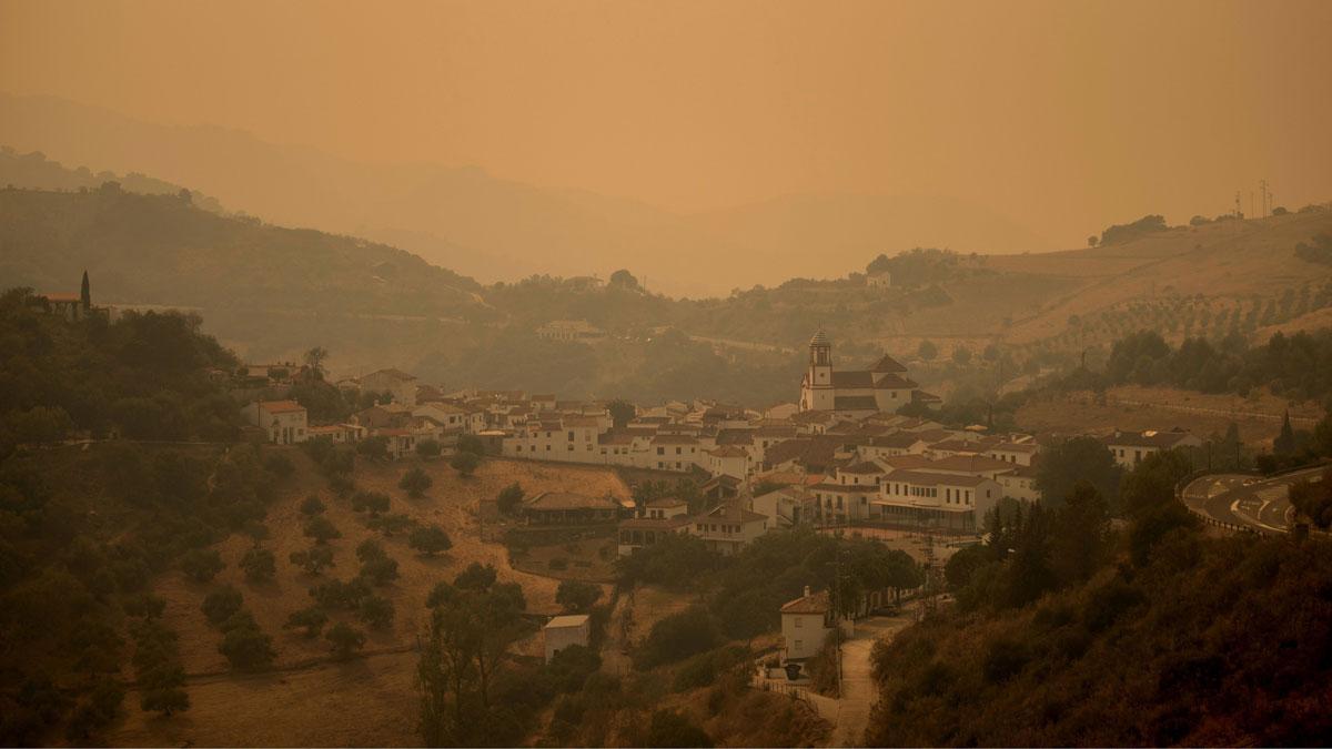 El incendio de Sierra Bermeja (Málaga) ya afecta a 7.400 hectáreas. En la foto, la población de Atajate, envuelta en humo, a causa del fuego.