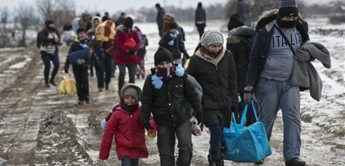 Familias de refugiados, muchos procedentes de Oriente Próximo, llegan a pie a Serbia, para continuar su viaje hacia Europa occidental, este lunes.