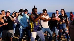 Gente bailando en la playa de la Barceloneta sin respetar las medidas de seguridad del covid.