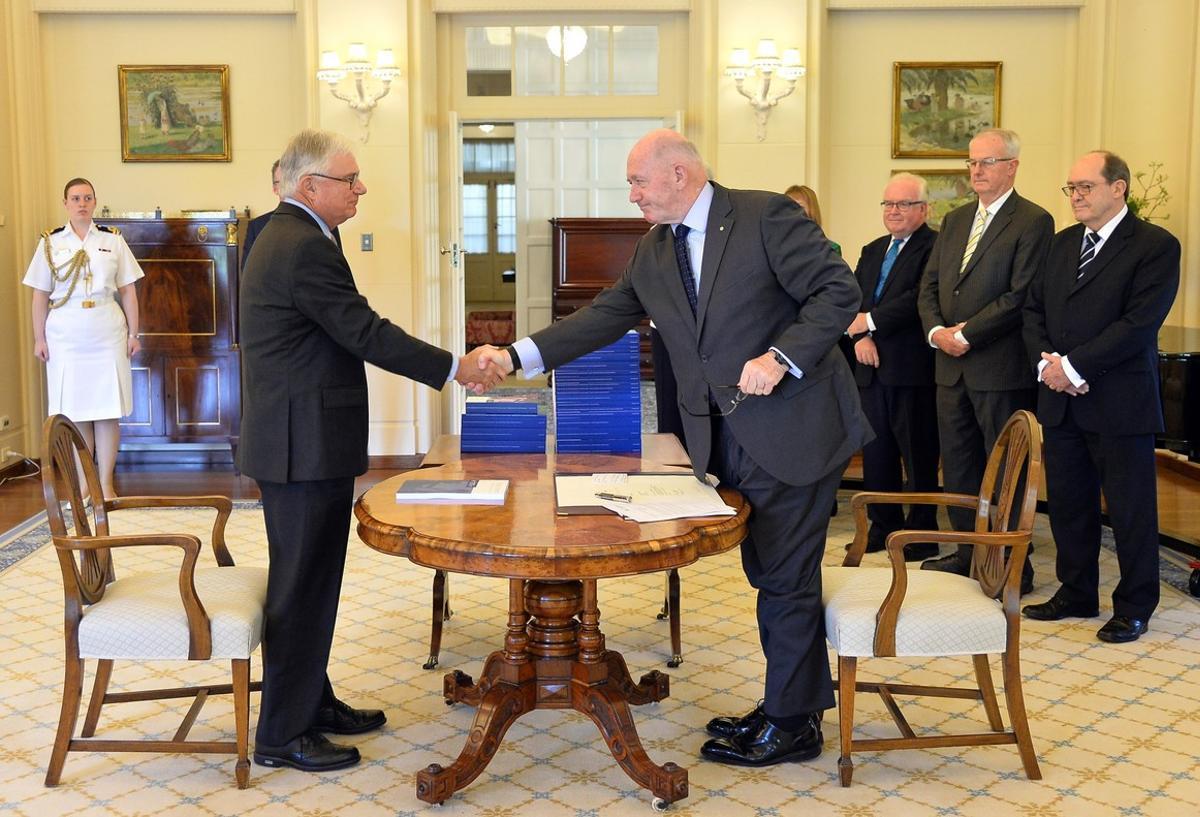 El comisionado de Justicia Peter McClellan (izquierda), y el gobernador general de Australia, Peter Cosgrove, se dan la mano tras la firma del documento final de la comisión especial de la pederastia en Australia.