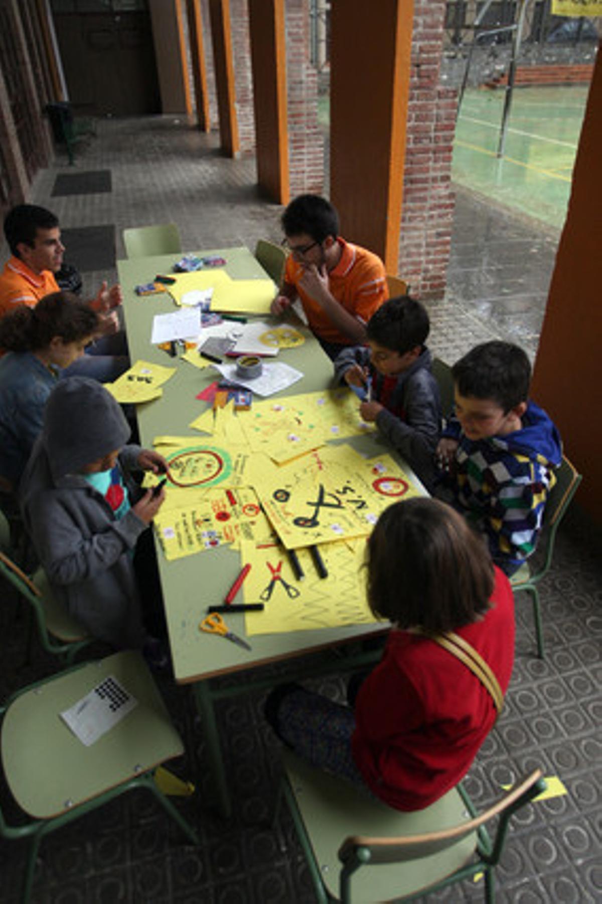 Un grupo de niños realiza trabajos manuales durante el encierro en el colegio La Sedeta, ayer en Barcelona.