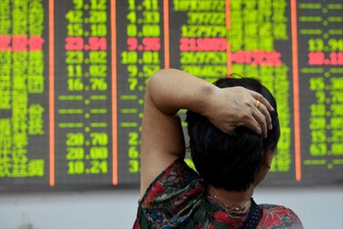 Un inversor mira el panel electrónico de las cotizaciones de la bolsa en Hangzhou, ayer.