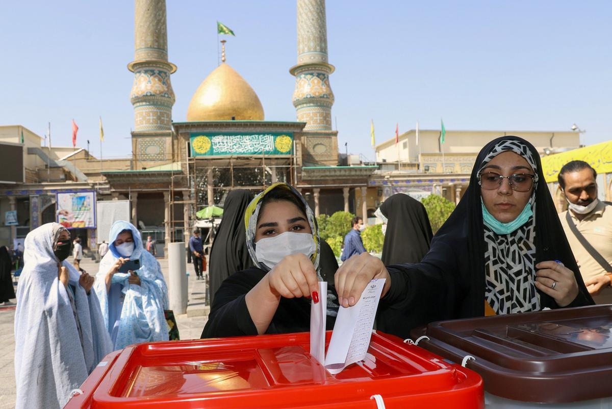 Dos mujeres depositan su voto en una urna en Teherán en las elecciones presidenciales de Irán.