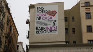 Gran pancarta contra los problemas inmobiliarios de Barcelona, en la plaza dels Àngels.