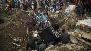 Un grupo de hombres localiza el cadáver de una mujer tras las inundaciones en la provincia de Parwan, este miércoles.