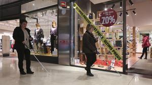 Dos discapacitados visuales pasean por el centro comercial Las Arenas de Barcelona, donde han instalado sensores que sirven para guiarles.