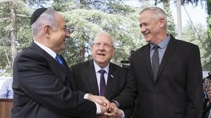 Netanyahu (izquierda) y Gantz (derecha) simbolizan el acuerdo junto al presidente de Israel, Reuven Rivlin.