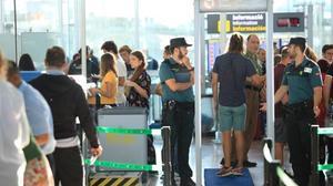 Un usuario pasa bajo el arco de detección de metales de la T-1 del aeropuerto de El Prat ante la mirada de dos guardias civiles.