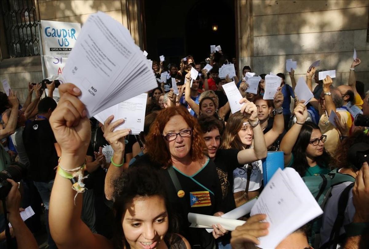 Varios estudiantes salen de la Universidad de Barcelona, con papeletas del referendum.