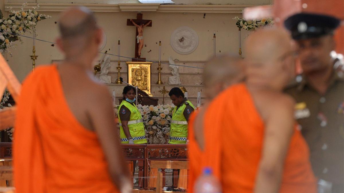Miembrosl de seguridad inspeccionan el interior de la Iglesia de San Sebastián observados por monjes budistas.